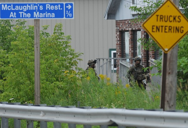 Maine State Police tactical team members maneuver into place off Main Road North in Hampden Friday, July 27, 2012.