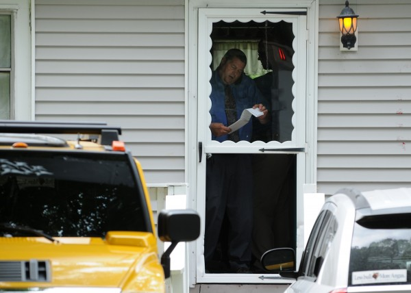 Maine State Police Detective Brian Strout flips though his notebook while on the phone inside 10 Marina Road in Hampden on Friday, July 27, 2012 while investigating a murder-sucide at that address.