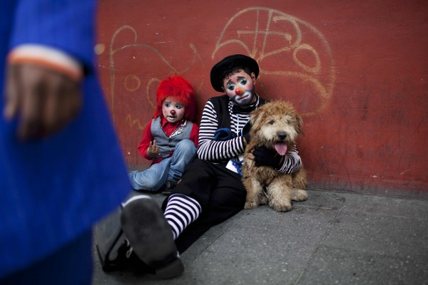 Two clowns take a rest on a sidewalk during the inauguration of the fourth annual Latin American Clown Congress in Guatemala City on Tuesday, July 24, 2012. Clowns from Central America and South America and the Caribbean have gathered for three days in the capital city to exchange ideas and attend workshops.