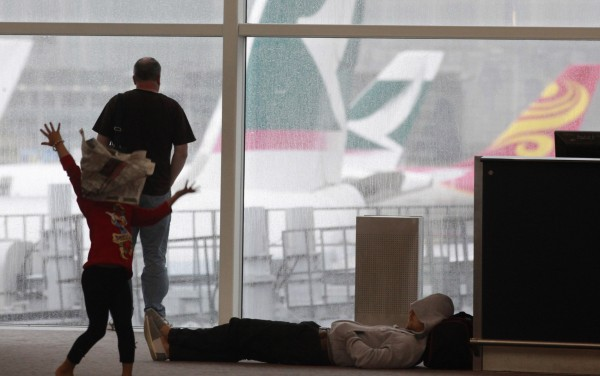 A girl dances with a newspaper to entertain herself after a night stranded at the airport by Typhoon Vicente in Hong Kong on Tuesday morning, July 24, 2012. Hundreds of passengers spent a night at the airport in Hong Kong after heavy rain and strong winds grounded planes.
