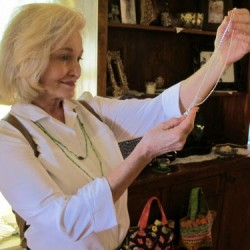 Dr. Bonnie Kline of Bucksport inspects a silver cross necklace during the town's first Cash Mob, organized by the Bucksport Bay Area Chamber of Commerce, at Bittersweet Gift Shop on Friday, July 27, 2012.