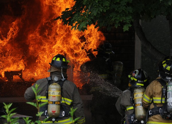 A firefighter is faced with a wall of flames as he breaks the glass on a residence at 289 West Etna Road in Etna on Monday, July 23, 2012.
