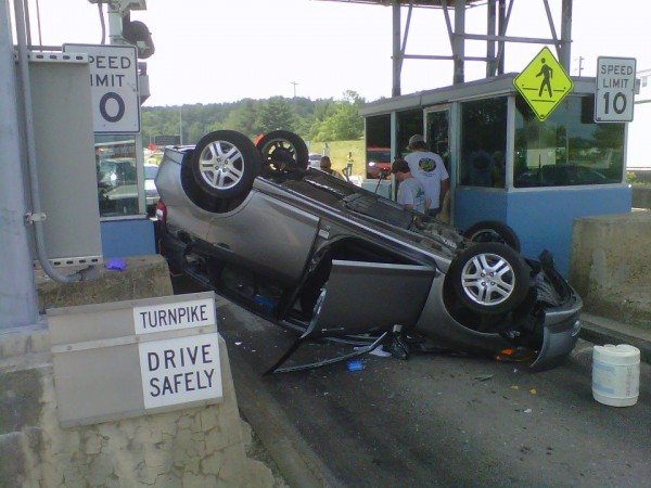 A Falmouth woman hit a concrete barrier at a tollbooth Monday afternoon, flipping her vehicle upside-down.