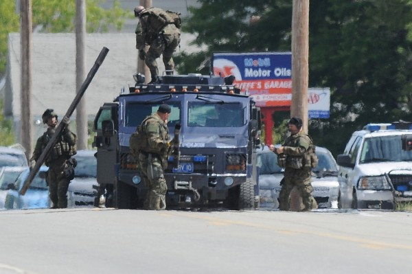 Maine State Police tactical team members unload a battering ram from their armored vehicle on Main Road North in Hampden Friday.