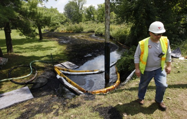 A worker monitors the water in Talmadge Creek in Marshall Township, Mich., near the Kalamazoo River as oil from a ruptured pipeline, owned by Enbridge Inc, is vacuumed out the water. The pipeline rupture spilled more than 800,000 gallons of crude oil into the river nearly two years ago.