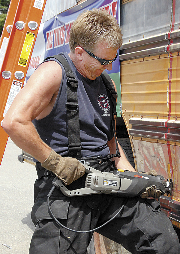 Bangor Fire Department Lt. David Dow battles the vibrating reciprocating saw and the metal side of a school bus as he makes the final cut at N.H. Bragg & Son on Thursday, June 28.