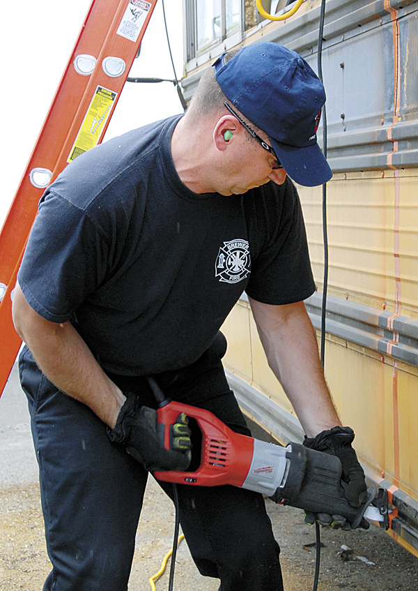 Representing the Brewer Fire Department, firefighter-EMT Bill Reaviel uses a Milwaukee reciprocating saw as he cuts open a school bus during a June 28 competition held at N.H. Bragg & Sons.