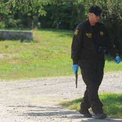 A Penobscot County Sheriff's Department officer removes a handgun from a Johnson Mill Road home that police responded to Sunday morning, July 22, 2012, after reports of a fire and gunshots.
