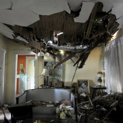 Frances Lukens looks at the tangle of boards and tree limbs piercing her living room ceiling in Lynchburg, Va., Saturday, after a huge oak tree fell on the house during a storm the previous night.