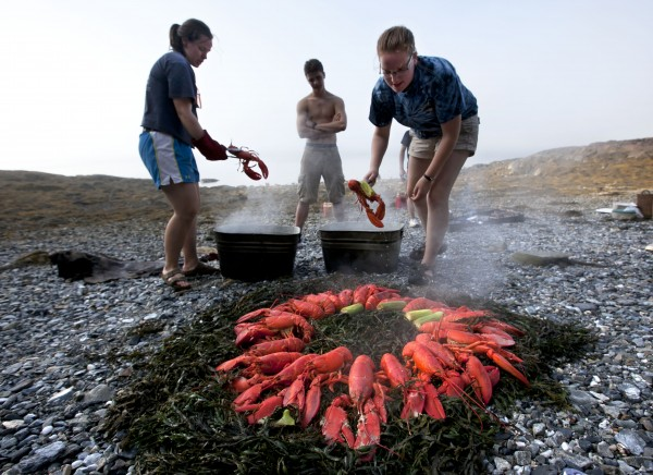 Maggy Mulhern (left) and Katharine Mead prepare a lobster bake for dinner on the shore of a small island in Penobscot Bay Thursday, August 2, 2012.