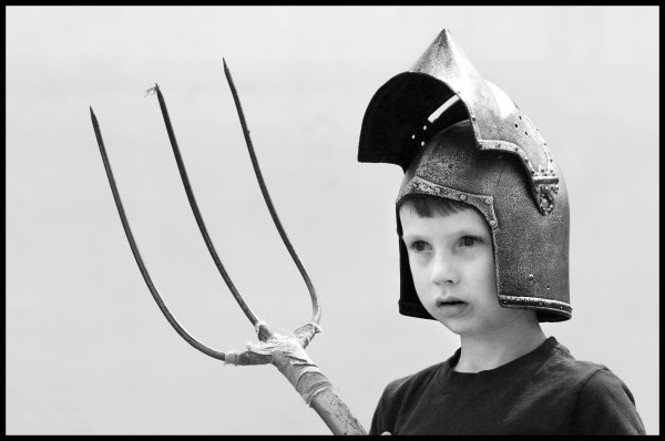 Desmond Robinson, 5, of Solon wears a knight's helmet and holds the pitchfork his Uncle Tony Robinson used in the sheaf-tossing competition at the Highland Games.