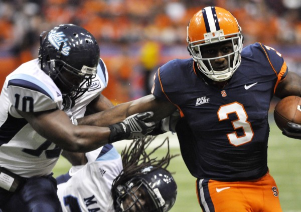 Maine linebacker Donte Dennis (left) tackles Syracuse's Delone Carter during a game two seasons ago. After missing last season due to injury, Dennis returns this season to lead the Maine defense.