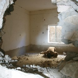 A sunni insurgent prays in a bombed out safe house in Ramadi, Iraq, November 2003.