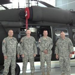 Chief Warrant Officer 4 Rick Chagnon (left), Sgt. 1st Class Art Ward, Lt. Col. Mark Sullivan and Sgt. 1st Class Pat Casha stand next to a new HH-60 Black Hawk at Bangor's Army Aviation Support Facility, a part of the Maine Army National Guard.