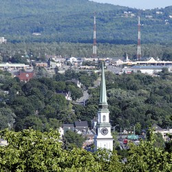 The spire and clock of Hammond Street Congregational Church in Bangor are backdropped by Brewer, where the Brewer Shopping Center is visible at right. The Wilson Street business district is visible in the center, the Twin City Plaza at left.