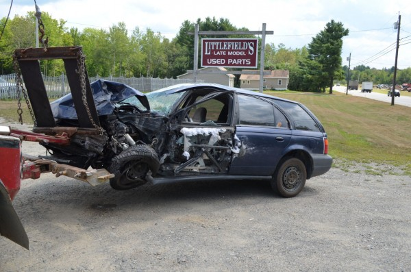 A Saturn station wagon is hooked to the back of a tow truck after being involved in a three-vehicle crash on Route 7 in Corinna on Thursday, Aug. 9, 2012.