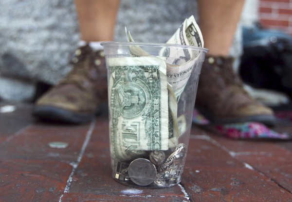A tip cup sits on the sidewalk in front of a street performer Sunday, August 26, 2012, in Portland. Every performer hopes to make a few bucks &quotbut once it becomes a job, it's just not as much fun,&quot said one musician.