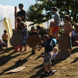 Parents watch as children slide on cardboard down a grassy hill on Sunday, Sept. 23, 2012, during the 36th annual Common Ground Country Fair in Unity.