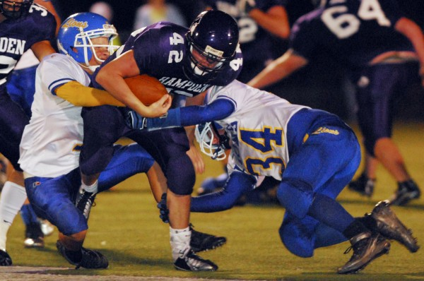 Belfast's Jordan Hill (7) (from left) and Baxter Smith (34) look to stop Hampden's Nick Jesiolowski (42) from any more yards durung second-period action at Hampden on Friday evening, Sept. 21, 2012.