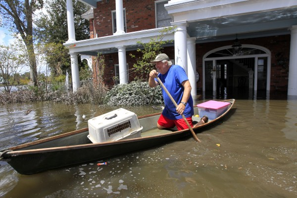 Don Duplantier paddles a pirogue from his flooded home as floodwaters from Hurricane Isaac recede in Braithwaite, La., on Sunday, Sept. 2, 2012. Duplantier had retrieved his cat and had collected his daughter's bridesmaid dress for the coming wedding of his son.