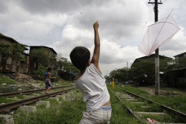 A Filipino boy flies his kite as he plays along the railroad tracks in suburban Manila, Philippines, on Sunday Sept. 2, 2012.