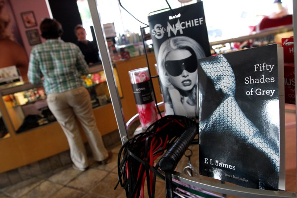 Hustler Hollywood displays the &quotFifty Shades of Grey&quot trilogy with S&M mask, whip and rose pedals on display near the checkout line, July 30, 2012, in South Florida.