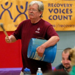 Bruce Campbell, clinical director of Wellspring, beats on a bucket during a drumming circle to introduce the Bangor Area Recovery Network's fifth annual summit on addiction recovery at the Brewer Auditorium on Wednesday morning, Sept. 26, 2012. The purpose of the summit is to &quotstimulate public visibility and show that people do recover,&quot said Campbell.