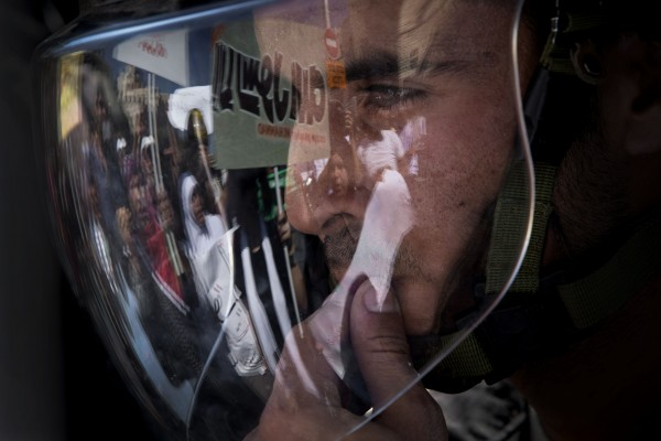 Demonstrators are reflected on the visor of an Israeli police during a protest in Jerusalem on Friday, Sept. 14, 2012, as part of widespread anger across the Muslim world about a film ridiculing Islam's Prophet Muhammad.