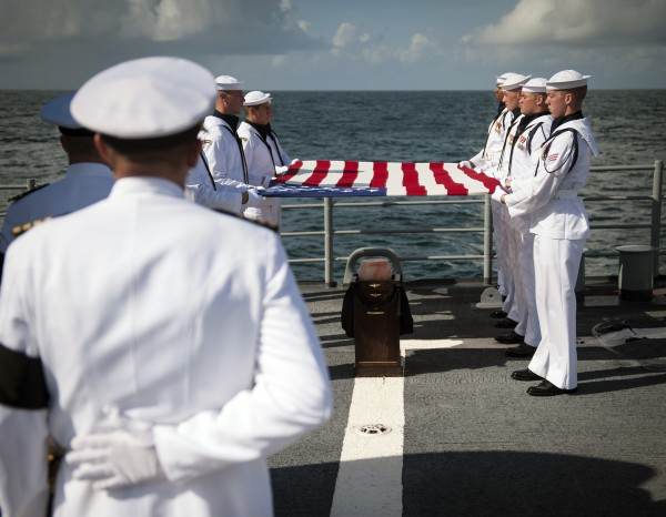 Members of the U.S. Navy ceremonial guard hold a United States flag over the remains of Apollo 11 astronaut Neil Armstrong during a burial at sea service aboard the USS Philippine Sea (CG 58), Friday, Sept. 14, 2012, on the Atlantic Ocean. Armstrong, the first man to walk on the moon during the 1969 Apollo 11 mission, died Aug. 25. He was 82.