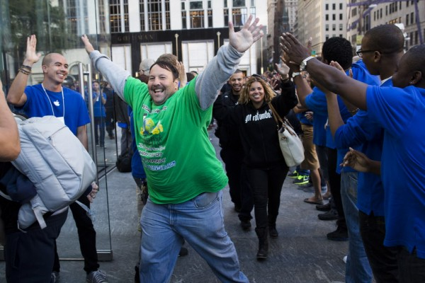 Greg Packer, 49, celebrates as he enters the Fifth Avenue Apple store for the release of the iPhone 5 on Friday, Sept. 21, 2012, in New York. Hundreds of people waited in line through the early morning to be among the first to get their hands on the highly anticipated phone.