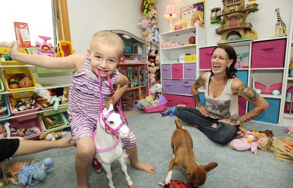 Five-year-old Danika DeMayo enjoys some playtime with her mother, Amy Liberman of Woodstock, on Sunday. Danika was seriously injured in an accident last month when the car driven by her mother was struck from behind. Danika suffered skull fractures and was in a coma as a result.