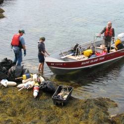 Pat Welch and Emma Pope-Welch prepare to load collected trash onto a Maine Island Trail Association boat while Henri Gignoux maneuvers the boat into position off Placentia Island on Saturday, Sept. 8, 2012.