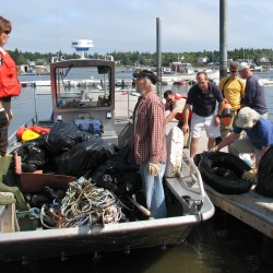 Volunteers unload trash from a U.S. Fish & Wildlife boat at a public boat launch in the Tremont village of Bernard on Saturday, Sept. 8, 2012.