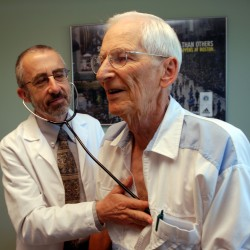 In this June 19, 2012 photo, Dr. Bruce Stowell examines patient Robert Busch at his office in Grants Pass, Ore. Stowell is among many doctors in rural areas who have capped the numbers of Medicare patients they take due to low reimbursement levels. A nationwide shortage of primary care physicians willing to set up practice in rural areas is making the problem worse.