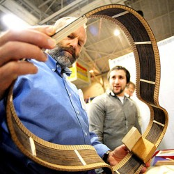 Richard Frost, left, of Maritime Applied Physics Corp., is shown part of the process of guitar-making by James Witkus, a luthier at Pantheon Guitars in Lewiston, on Wednesday during the Maine Technology Institute's mixer at the Androscoggin Bank Colisee.