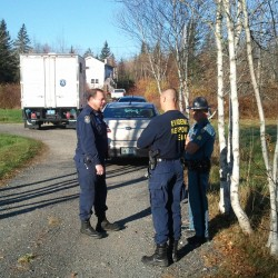 Maine State Police officers stand in the driveway of the Robert Tilden and Russell Pinkham properties off Mud Creek in Lamoine on Wednesday, Oct. 23, 2012.