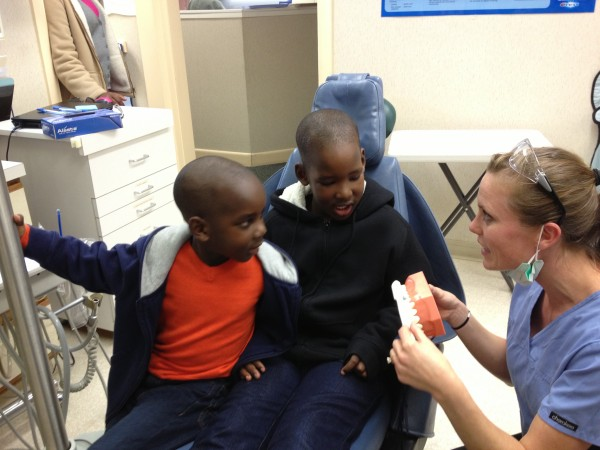 Patients Justin and Joel Kabera chat with Dental Assistant Rachael Creisher Tuesday night at Portland's Bright Smiles clinic at Community Dental on Brighton Avenue.