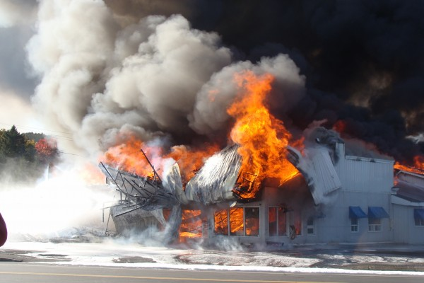 Flames burst out as parts of the wall at Valley Auto in Fort Kent collapse on Wednesday, Oct. 3, 2012.