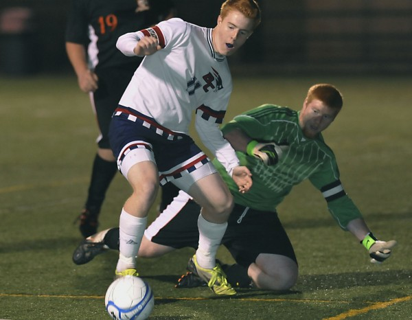 Bangor Christian boys soccer player Ben Bragg (11)  works the ball away from Ashland keeper J.J. Dozier in the first half of their game in Hampden, Maine, Wednesday, Oct. 31, 2012.