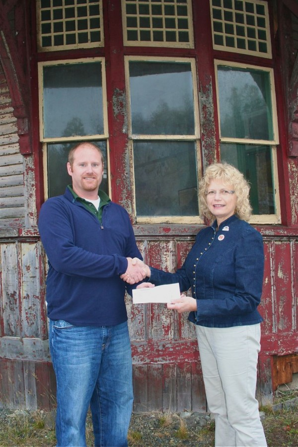 In front on the rounded section of Greenville Junction's railroad depot, Steve Pollis from Plum Creek hands a $2,000 check to Jane Hall, Chair of the Save the Depot project.