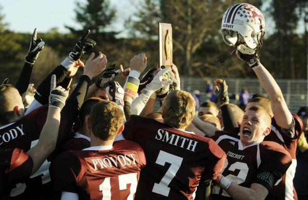 The Foxcroft Academy Ponies football team celebrates with the Class C Eastern Maine trophy on Saturday, Nov. 10, 2012, after defeating John Bapst 33-7 at Dover-Foxcroft.