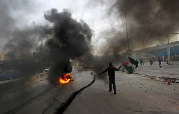 A Palestinian stone-thrower walks past smoke from burning tyres during clashes with Israeli security forces against Israel's military operation in Gaza, at Qalandia checkpoint near the West Bank city of Ramallah November 16, 2012. Palestinian militants nearly hit Jerusalem with a rocket for the first time in decades on Friday and fired at Tel Aviv for a second day, in a stinging challenge to Israel's Gaza offensive after an Egyptian bid to broker a truce.