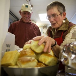 Jim Gillies and Nancy Barber, both volunteers, fill a bowl with rolls at the Bath Area Food Bank's thrice weekly free lunch in the basement of the First Baptist Church in Bath on Friday Nov. 9, 2012. The soup kitchen reopened three weeks ago after being shuttered for six weeks.