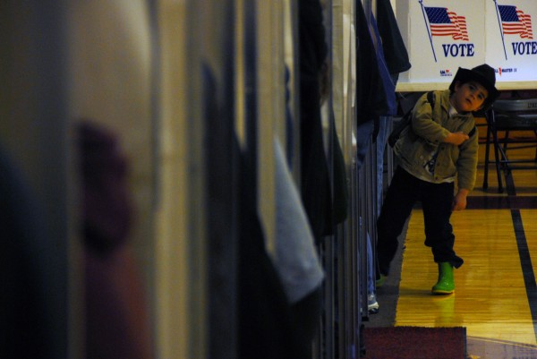 An unidentified boy whose mother is in a voting booth leans out and looks around at Mattanawcook Academy in Lincoln on Election Day, Nov. 6, 2012.