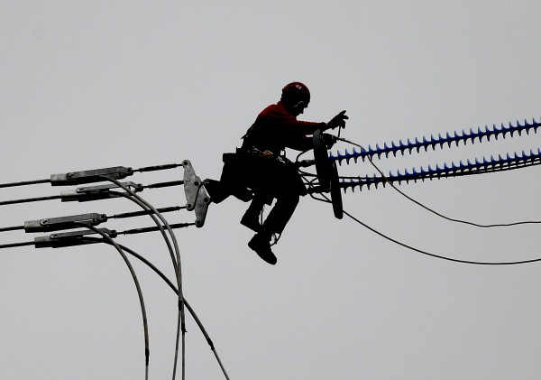 A worker is silhouetted against the sky as he straddles new overhead electric power lines at a high altitude in Dortmund, Germany, Monday, Nov. 5, 2012. Some 2,237 miles of new power cables are planned in Germany to force the energy turnaround to use alternative sources. The German utilities' industry association BDEW said Monday the solar power output from January through September rose from 16.5 gigawatt hours last year to 25 gigawatt hours in 2012. Germany decided last year to phase out nuclear power by 2022 and replace it with renewable energies.
