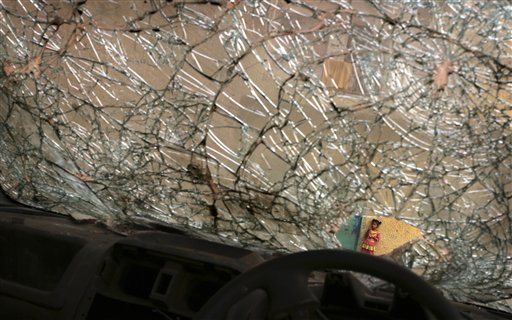 An Indian girl is seen through  the broken window of an abandoned and damaged car in a poor neighborhood of New Delhi, india, Tuesday, Nov. 6, 2012.