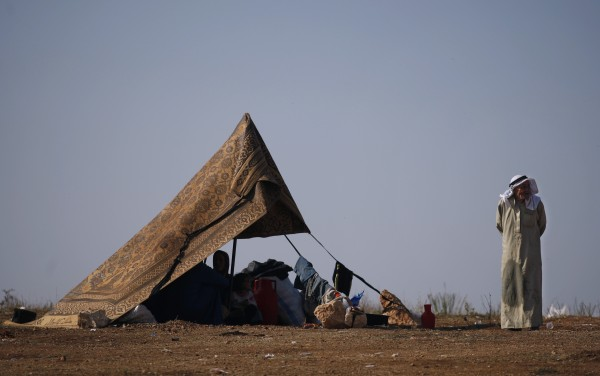 A Syrian family who fled from the violence in their village, sit in a tent at a displaced camp, in the Syrian village of Atma, near the Turkish border with Syria, Monday, Nov. 5, 2012.