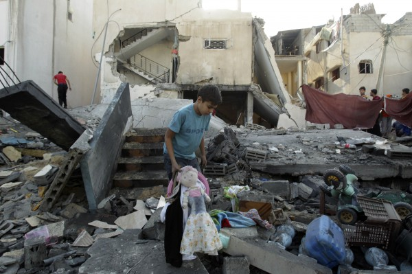 A Palestinian boy holds a doll as he walks amid the rubble of a destroyed house after what witnesses said was an Israeli air strike, in Rafah in the southern Gaza Strip November 20, 2012. U.S. Secretary of State Hillary Clinton headed to the region with a message that escalation of the week-long conflict was in nobody's interest.