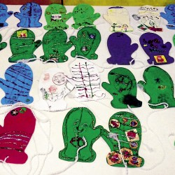 "Pairs of mittens decorated by third grade students at the Downeast School dry on a table in the school's lobby. The third grade classrooms participated in the ""Mittens From Maine"" community service project in conjunction with Changing Seasons Federal Credit Union."