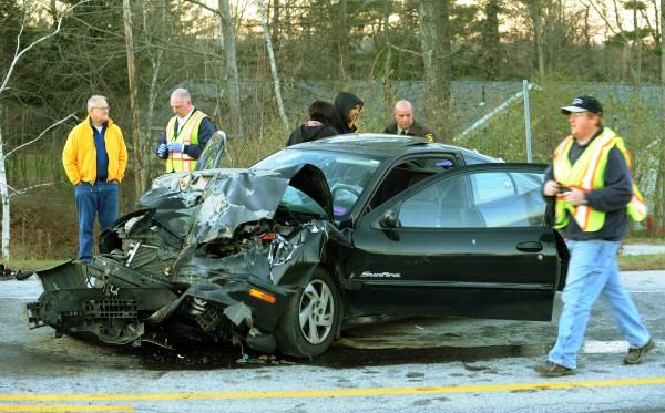 Orrington Fire Department personnel and Penobscot Deputy Sheriff James Kennedy, center, and bystanders surround a car driven by Kaitlyn Gravitt of Bucksport after it rear-ended a 1998 GMC pick-up truck driven by Lionel Ducas of Orrington at the intersection of Pleasant Hill road and Route 15 in Orrington on Monday, Nov. 19, 2012.